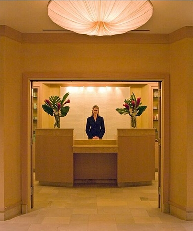 An employee stands behind a desk at a hotel lobby