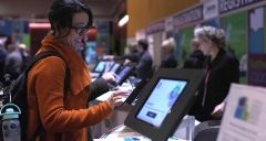 A woman using a kiosk to check in to an event
