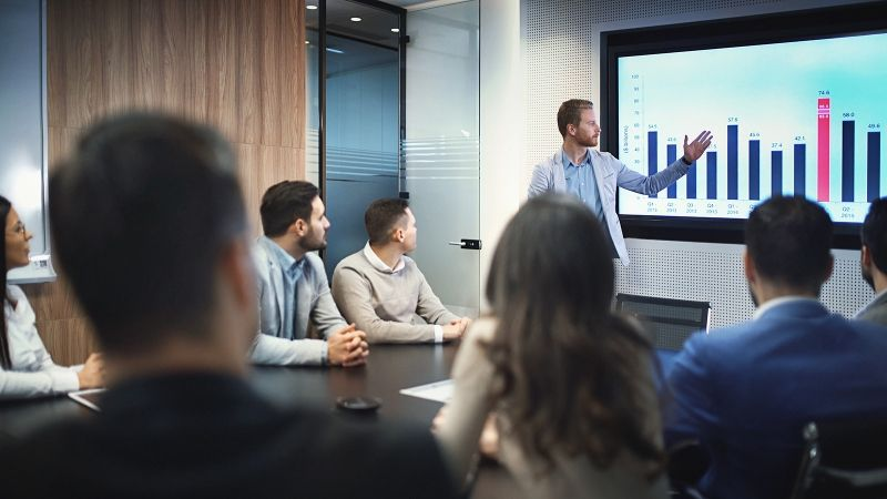 man pointing at powerpoint during sales presentation