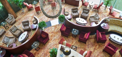 birds-eye view of hotel lobby with plants and club chairs